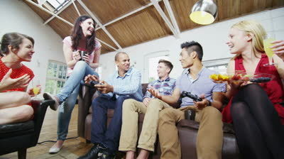 Stock footage happy mixed ethnicity group of friends socializing at home and playing video games