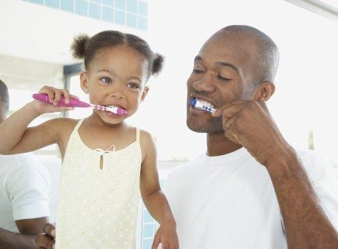 Father daughter brush teeth