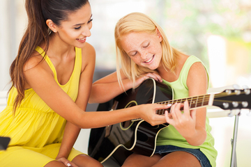 Small pic guitar teacher tutoring young girl